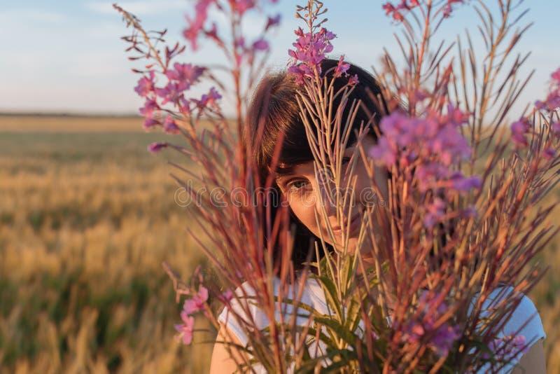 Muchacha hermosa en el campo que oculta detrás de las flores fotografía de archivo libre de regalías