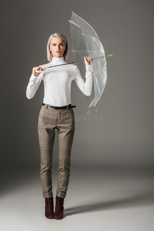 muchacha hermosa en el cuello alto blanco y los pantalones grises que sostienen el paraguas transparente fotografía de archivo libre de regalías