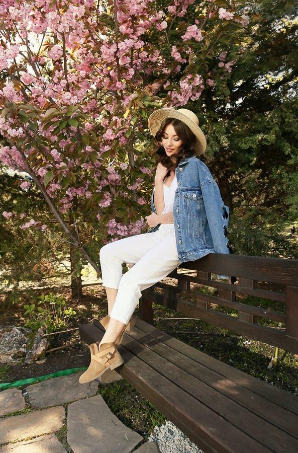 Muchacha hermosa en el equipo elegante que presenta en jardín del flor de la primavera fotos de archivo
