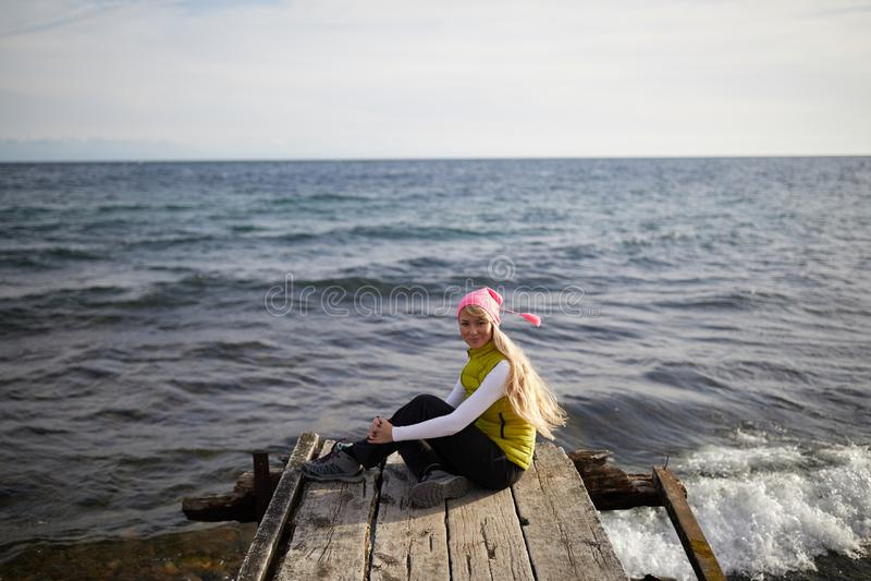 Muchacha hermosa en el estilo del mar que se sienta en el puente de madera Recorrido y vacaciones Concepto de la libertad Hermoso foto de archivo