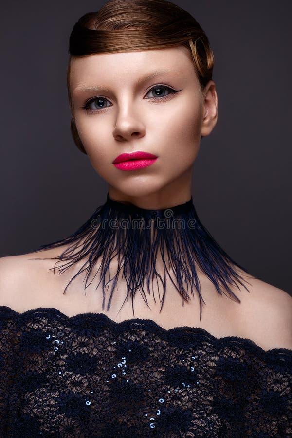 Muchacha hermosa en el estilo Gatsby con un cuello de plumas y del vestido azul del cordón Modele con el peinado a partir de los  foto de archivo