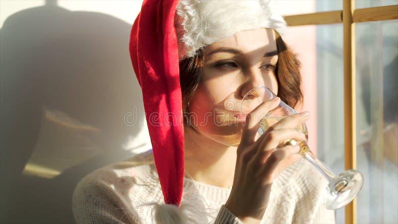 Muchacha hermosa en el sombrero de Santa Claus con un vidrio de champán que mira fuera de la ventana, del feliz Christmass y del  fotos de archivo libres de regalías