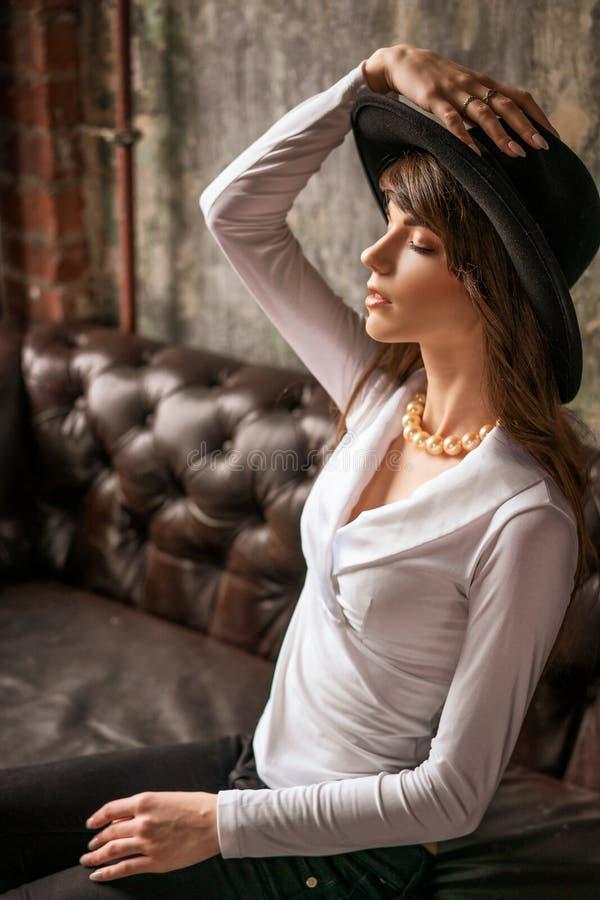 Muchacha hermosa en el sombrero negro que se sienta en el sofá, mujer elegante imágenes de archivo libres de regalías