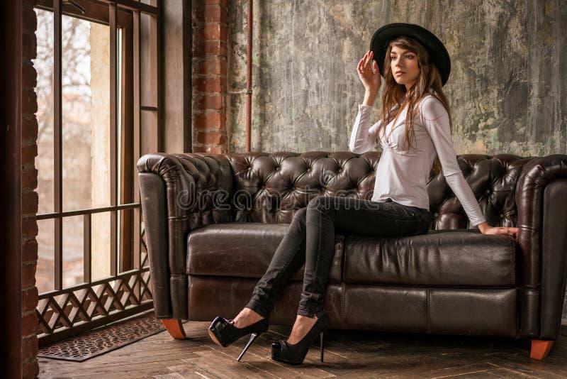 Muchacha hermosa en el sombrero negro que se sienta en el sofá, mujer elegante imagen de archivo