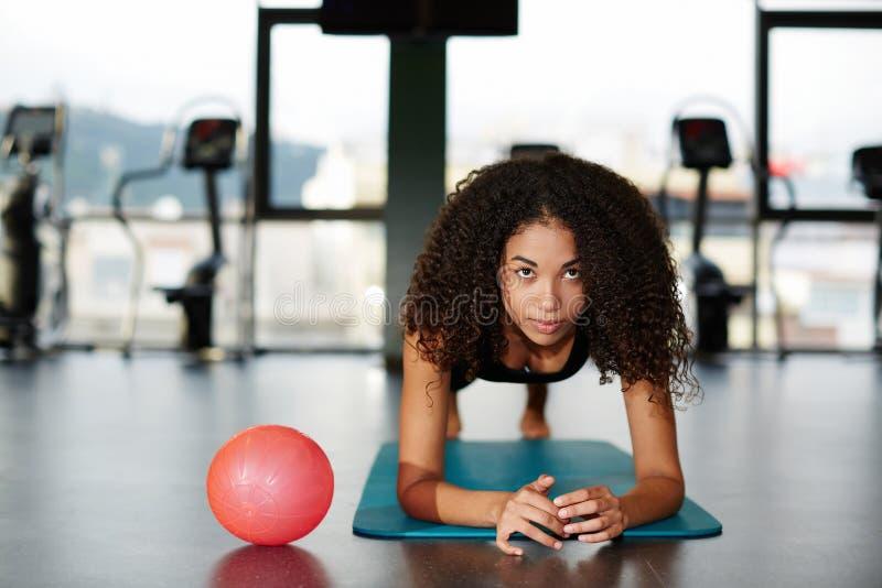 Muchacha hermosa en el sportswea que se inclina en sus codos que hacen el ejercicio para los abdominals en el gimnasio fotografía de archivo libre de regalías