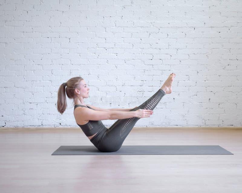 Muchacha hermosa en el traje gris de los deportes que hace entrenamiento en la matem?ticas, actitud cl?sica de la yoga del barco, fotografía de archivo