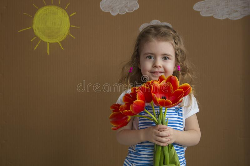 Muchacha hermosa en el vestido azul con los tulipanes de las flores en manos en un fondo ligero con el sol y las nubes pintados fotografía de archivo libre de regalías
