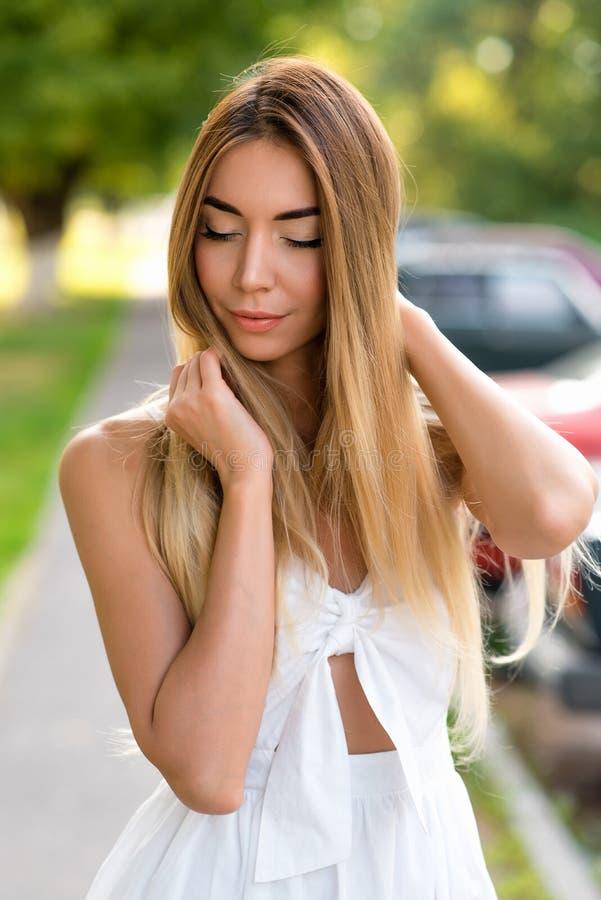Muchacha hermosa en el vestido blanco en la ciudad del verano en la calle Pelo largo del primer, piel bronceada, maquillaje diari imágenes de archivo libres de regalías
