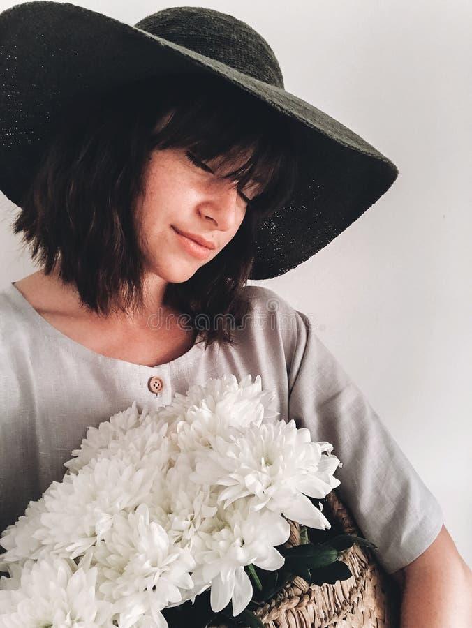 Muchacha hermosa en el vestido de lino y el sombrero que sostienen la cesta de la paja con las flores blancas, y tomando el selfi fotografía de archivo