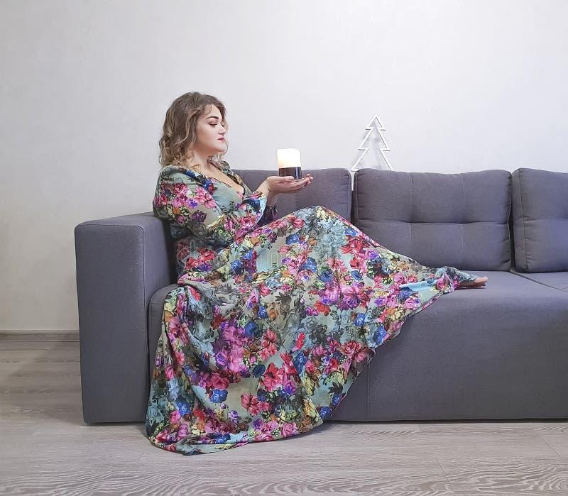 muchacha hermosa en el vestido, pelo rizado, sentada, sofá elegante fotografía de archivo