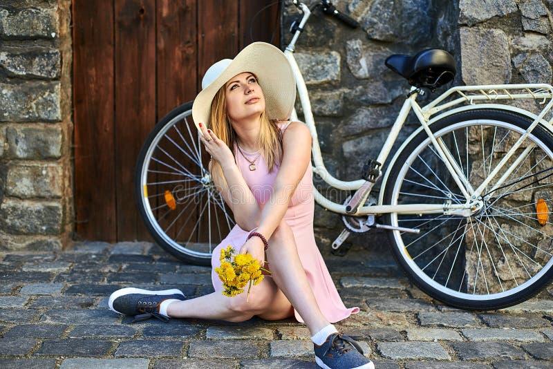 Muchacha hermosa en el vestido rosado, sombrero de paja que presenta el retrato que se sienta en el camino de piedra en ciudad vi imágenes de archivo libres de regalías