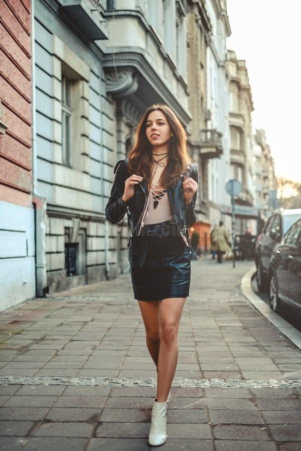 Muchacha hermosa en falda con la mochila que camina en la acera fotos de archivo