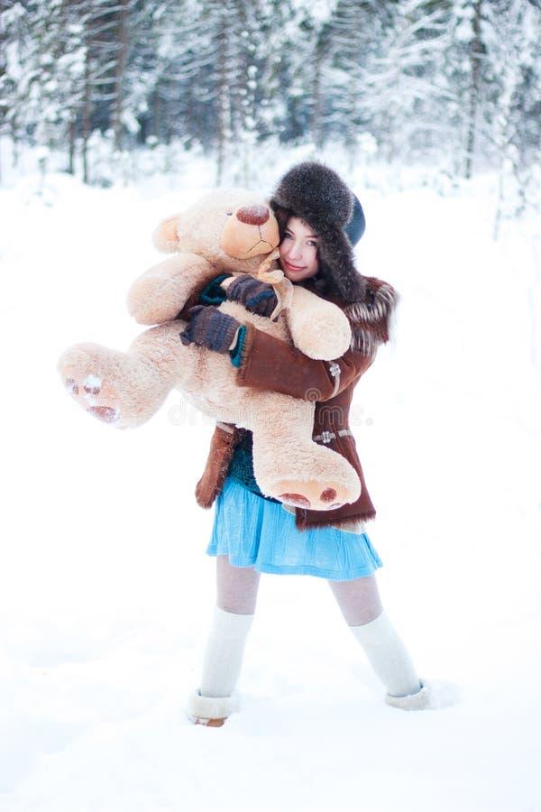 Muchacha hermosa en fondo nevoso del bosque del invierno con el oso de peluche fotografía de archivo