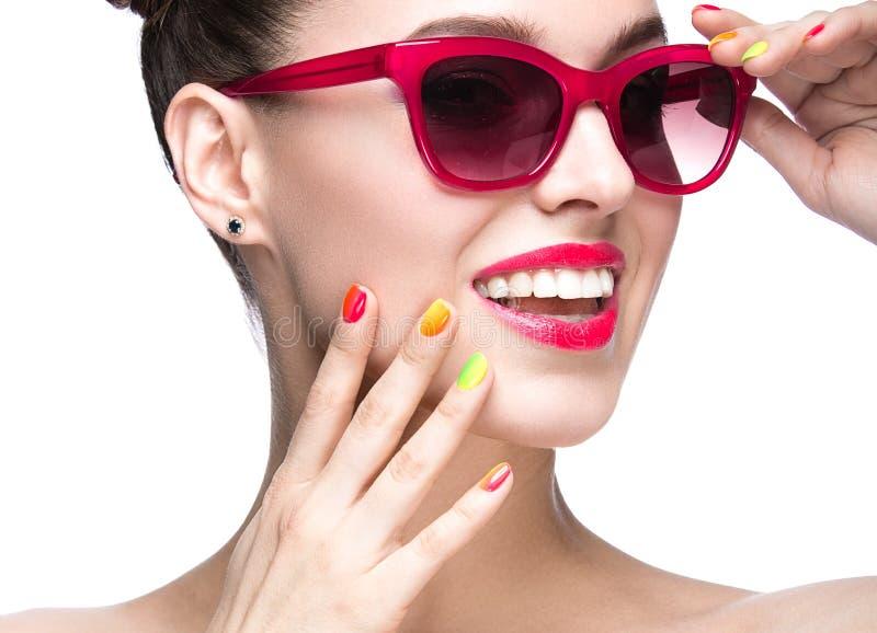 Muchacha hermosa en gafas de sol rojas con maquillaje brillante y clavos coloridos Cara de la belleza imagen de archivo