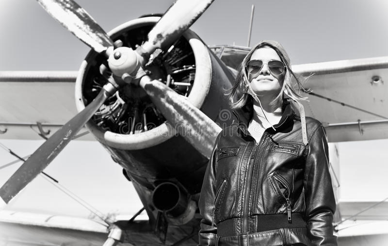 Muchacha hermosa en la chaqueta negra que se coloca en un avión de la guerra. imágenes de archivo libres de regalías