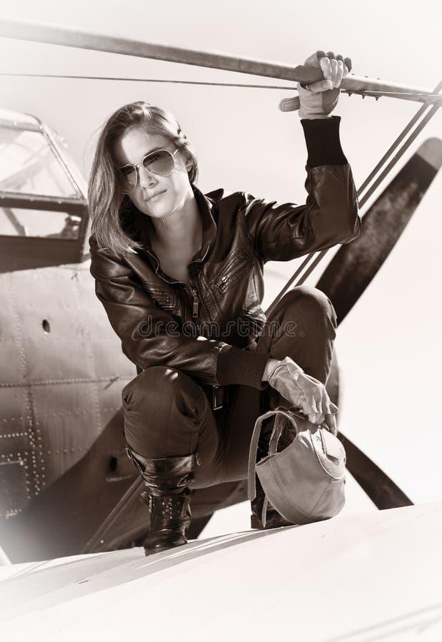 Muchacha hermosa en la chaqueta negra que se coloca en un avión de la guerra. imagen de archivo