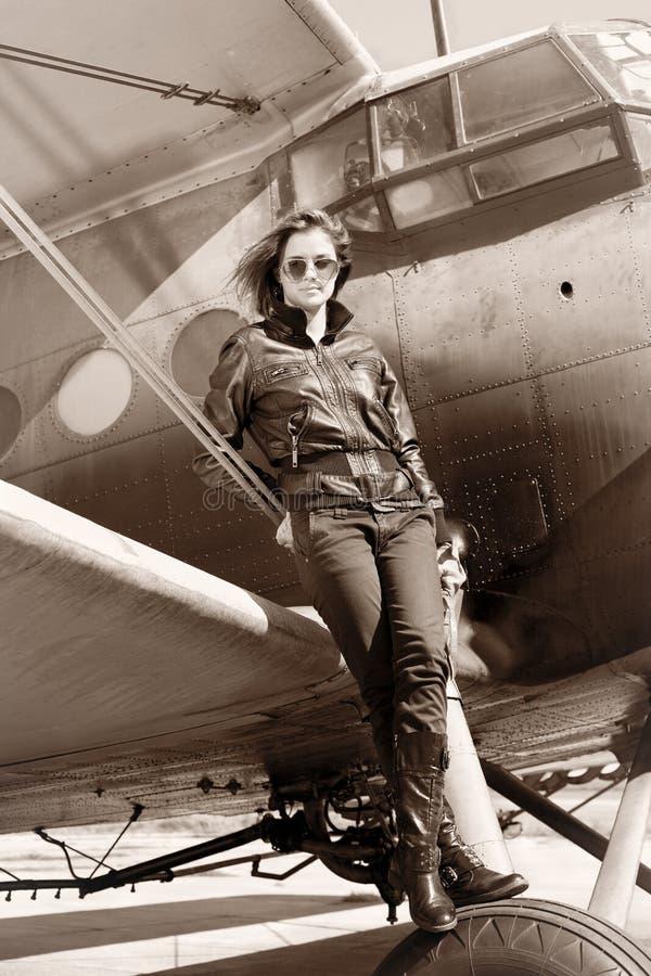 Muchacha hermosa en la chaqueta negra que se coloca en un avión de la guerra. foto de archivo