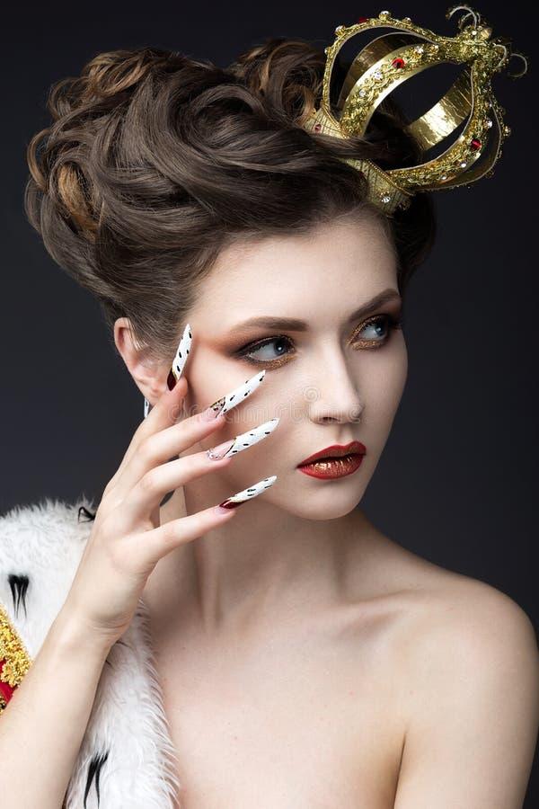 Muchacha hermosa en la imagen de la reina en la capa con una corona en la cabeza y los clavos largos Cara de la belleza foto de archivo libre de regalías