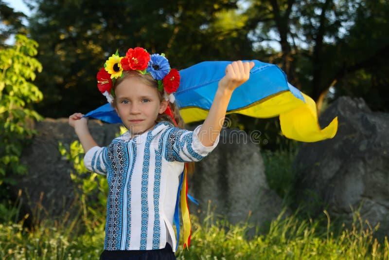 Muchacha hermosa en la ropa ucraniana tradicional que sostiene una bandera de Ucrania imagenes de archivo