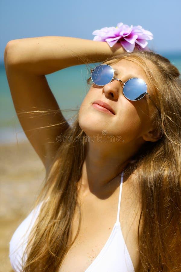 Muchacha hermosa en las gafas de sol que presentan en la playa imagen de archivo libre de regalías