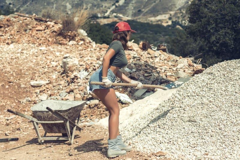 Muchacha hermosa en los pantalones cortos, camiseta y en el casquillo enarbolado rojo que aumenta para arriba una pala con grava imagenes de archivo
