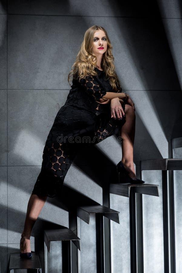Muchacha hermosa en negro en las escaleras foto de archivo