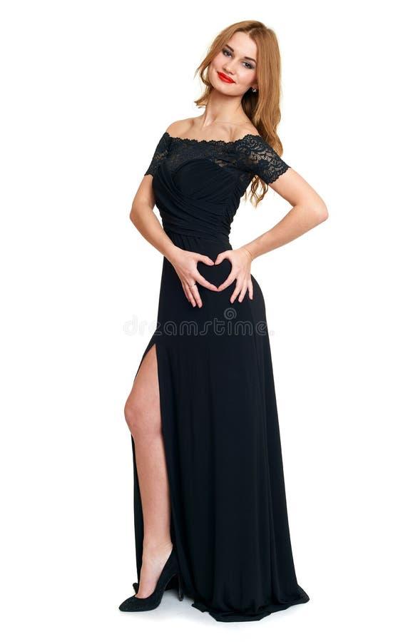 Muchacha hermosa en símbolo negro del corazón de la demostración del vestido de la mano, aislada en el fondo blanco, el día de fi fotografía de archivo