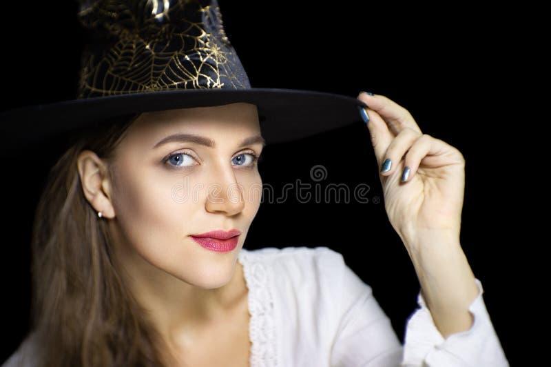 Muchacha hermosa en sombrero negro del mago fotografía de archivo