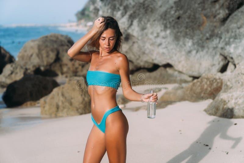 Muchacha hermosa en traje de baño azul en la botella de la tenencia de la playa de agua potable en su mano imagenes de archivo