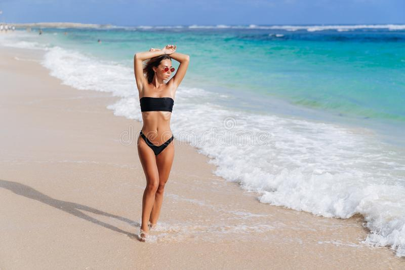 Muchacha hermosa en traje de ba?o negro y las gafas de sol que descansan cerca del oc?ano en la playa fotografía de archivo libre de regalías
