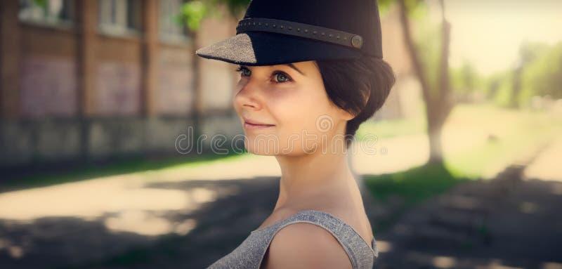 Muchacha hermosa en un casquillo negro Retrato de una muchacha imagenes de archivo
