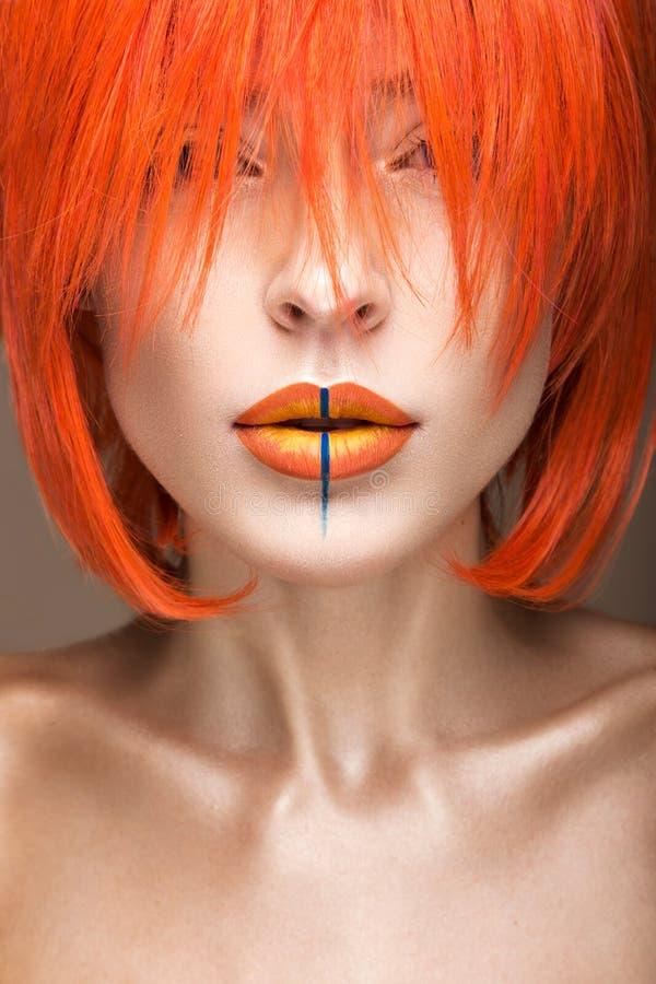 Muchacha hermosa en un estilo cosplay de la peluca anaranjada con los labios creativos brillantes Imagen de la belleza del arte fotos de archivo