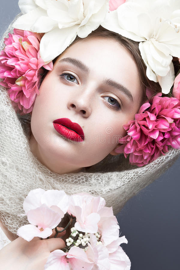 Muchacha hermosa en un pañuelo en el estilo ruso, con las flores grandes en sus labios principales y rojos Cara de la belleza imágenes de archivo libres de regalías