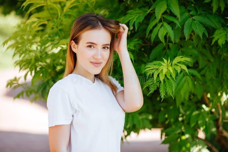 Muchacha hermosa en un parque verde imagenes de archivo