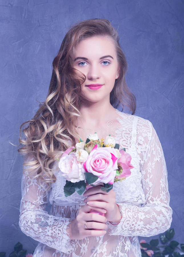 Muchacha hermosa en un peignoir blanco con un ramo de flores fotografía de archivo libre de regalías