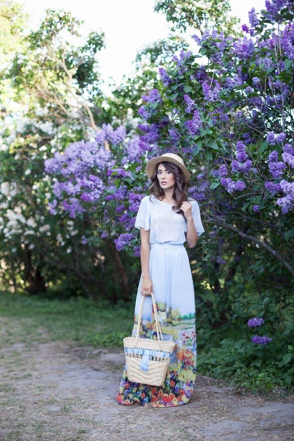 Muchacha hermosa en un sombrero de paja en un jardín de la lila Muchacha con las flores de la lila en tiempo de primavera Jardine fotos de archivo libres de regalías