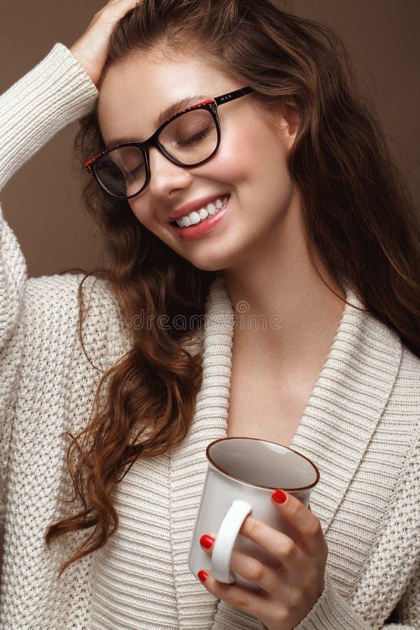 Muchacha hermosa en un suéter acogedor con una taza de té, los vidrios para la visión y los labios atractivos Cara de la belleza imagen de archivo