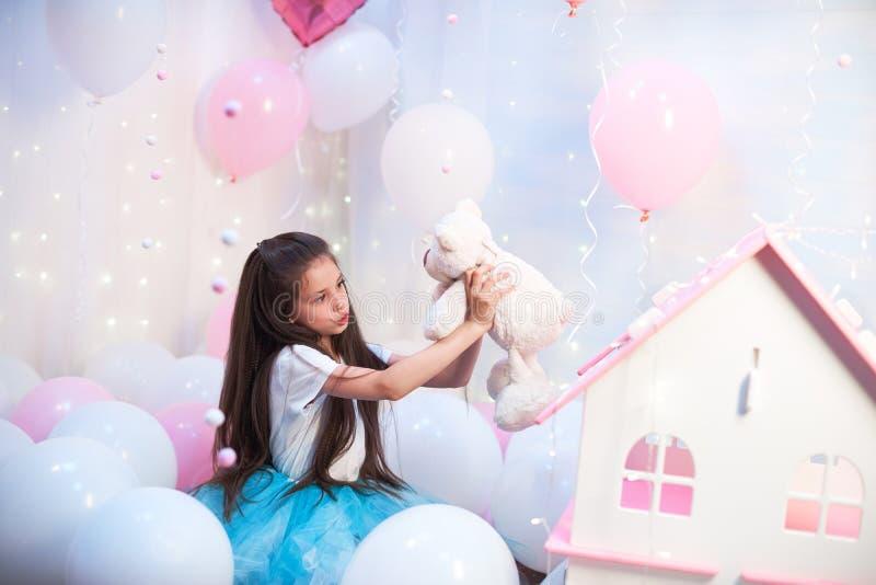 Muchacha hermosa en un tutú colorido de la falda enorme en el paisaje de los globos que se sostienen en juguete de la felpa de Ro fotografía de archivo