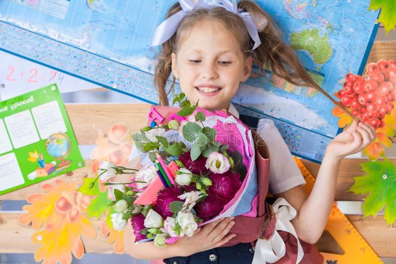 Muchacha hermosa en un uniforme escolar cerca de un consejo escolar con un ramo en manos fotografía de archivo