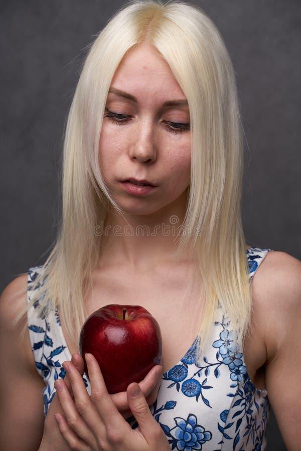 Muchacha hermosa en un vestido de moda con la manzana foto de archivo