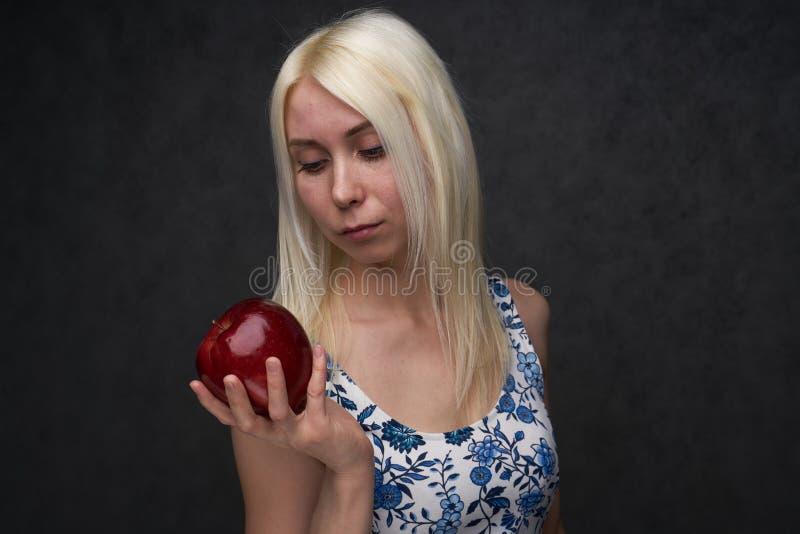 Muchacha hermosa en un vestido de moda con la manzana imagenes de archivo
