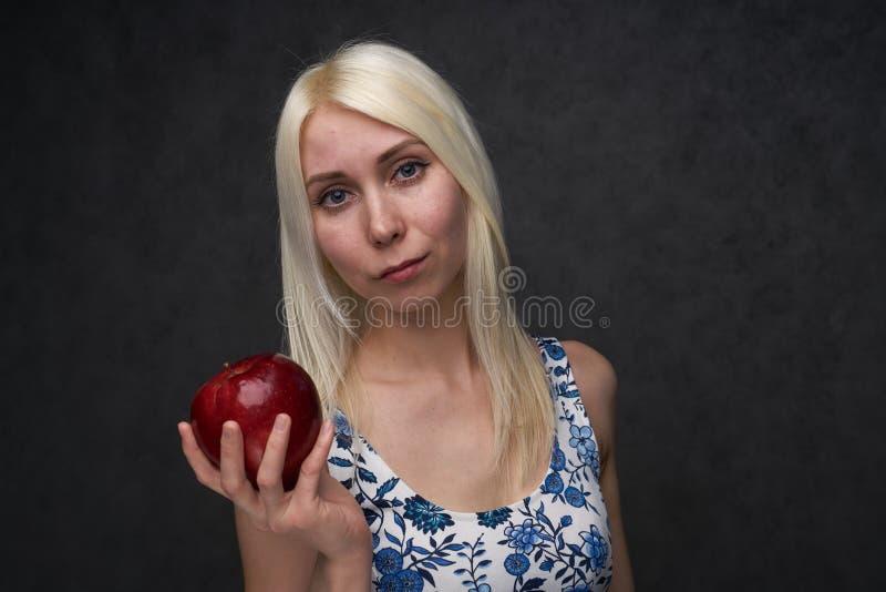 Muchacha hermosa en un vestido de moda con la manzana imágenes de archivo libres de regalías