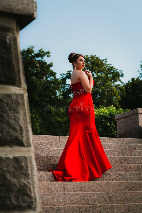 Muchacha hermosa en un vestido de noche rojo largo que se coloca en el fondo de árboles y de arbustos imagen de archivo