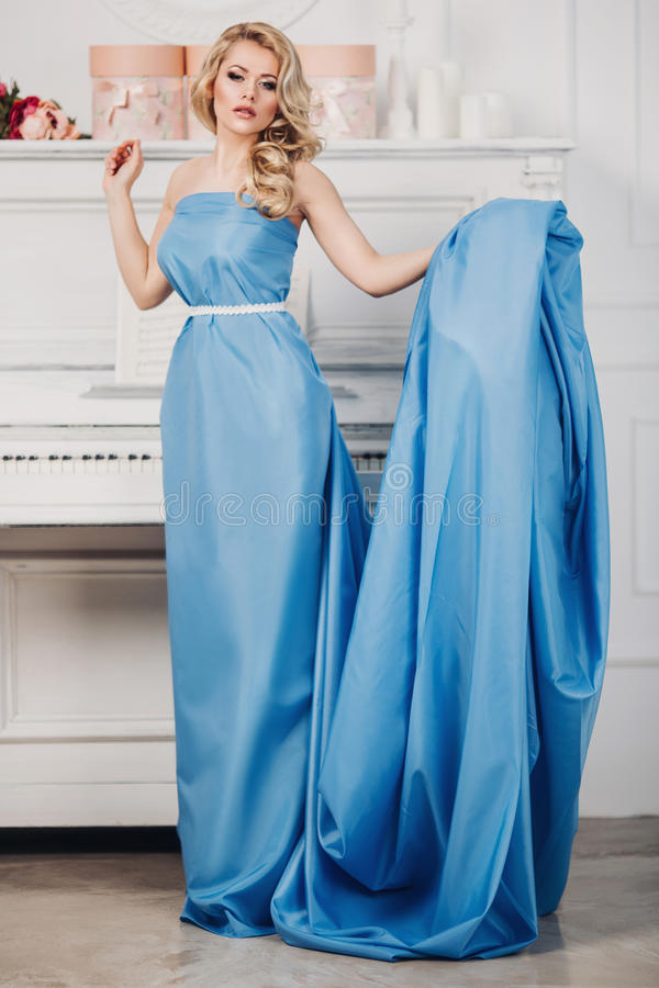 Muchacha hermosa en un vestido largo azul foto de archivo
