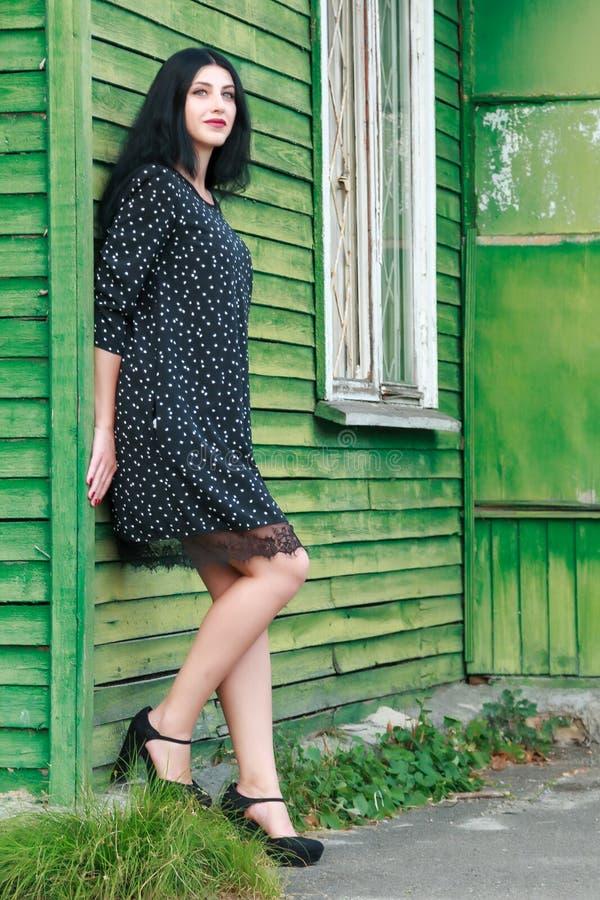 Muchacha hermosa en un vestido negro cerca de una casa verde vieja fotografía de archivo libre de regalías