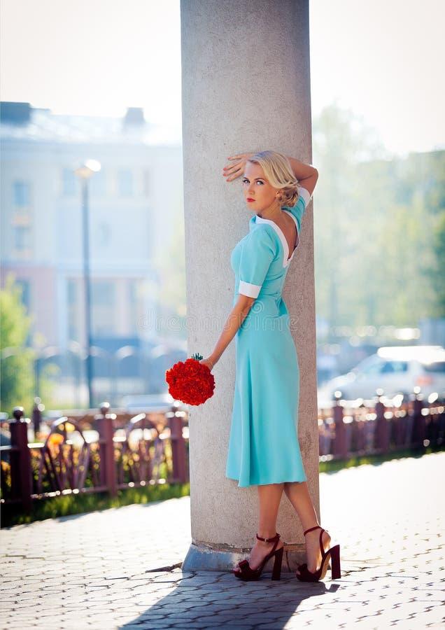 Muchacha hermosa en un vestido rosado con un ramo de fotos de archivo libres de regalías