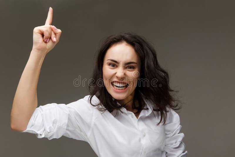 Muchacha hermosa en una camisa blanca con un finger aumentado para arriba En un fondo ligero imagenes de archivo
