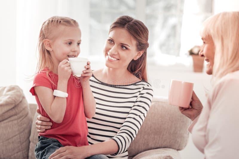 Muchacha hermosa en una camiseta roja que come té con su familia fotos de archivo