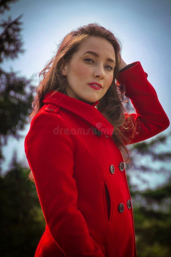 Muchacha hermosa en una capa roja en un fondo de árboles fotografía de archivo libre de regalías