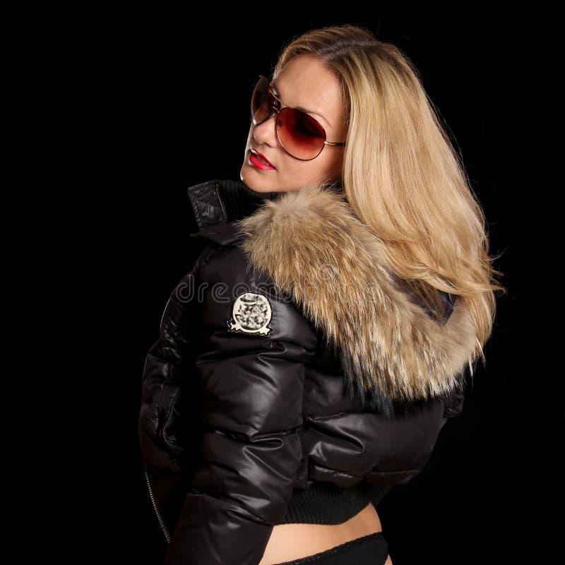 Muchacha hermosa en una chaqueta con un capo motor imágenes de archivo libres de regalías
